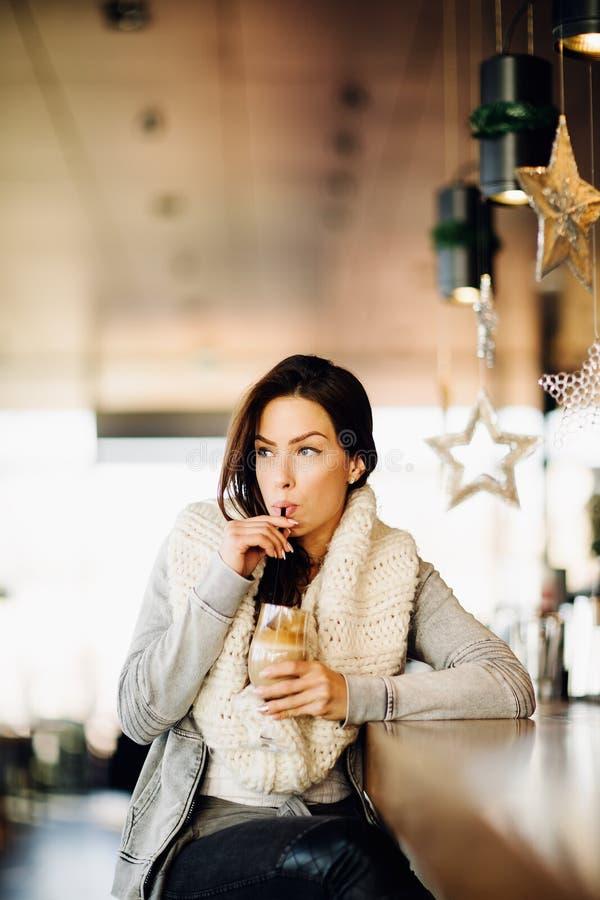 Portr?t einer jungen, attraktiven Frau, allein sitzend an einer Bar, trinkender Kaffee stockbilder