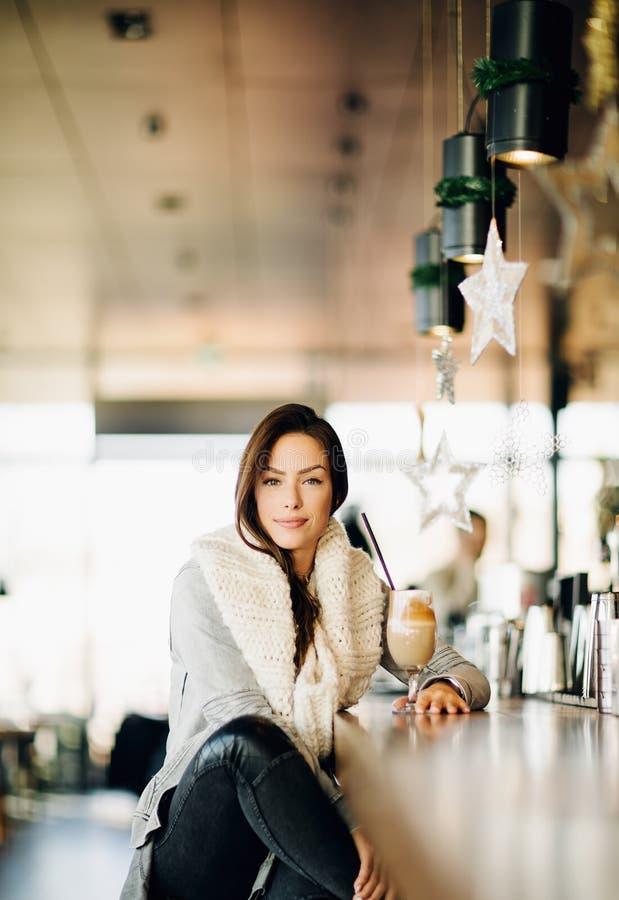 Portr?t einer jungen, attraktiven Frau, allein sitzend an einer Bar, trinkender Kaffee stockbild