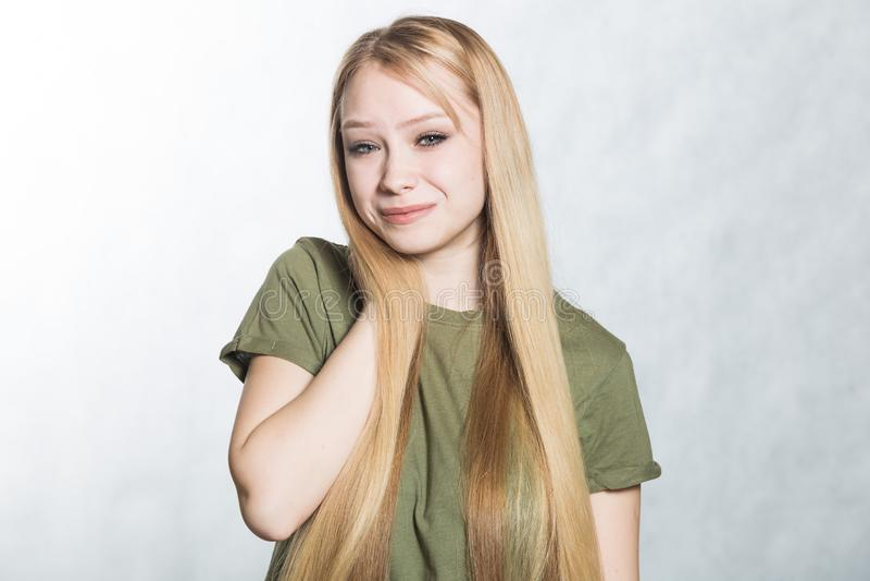 Portr?t einer jungen Frau mit der Hand auf Hals ?ber grauem Hintergrund lizenzfreies stockbild