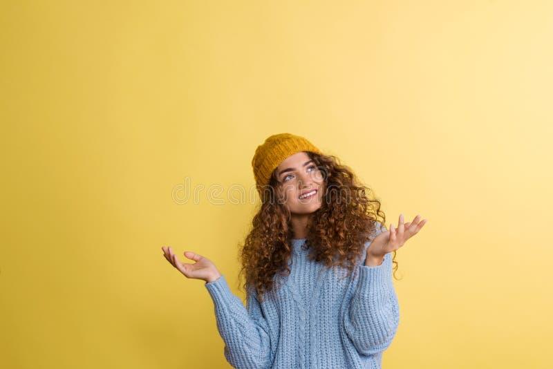 Portr?t einer jungen Frau mit woolen Hut in einem Studio auf einem gelben Hintergrund stockfotos