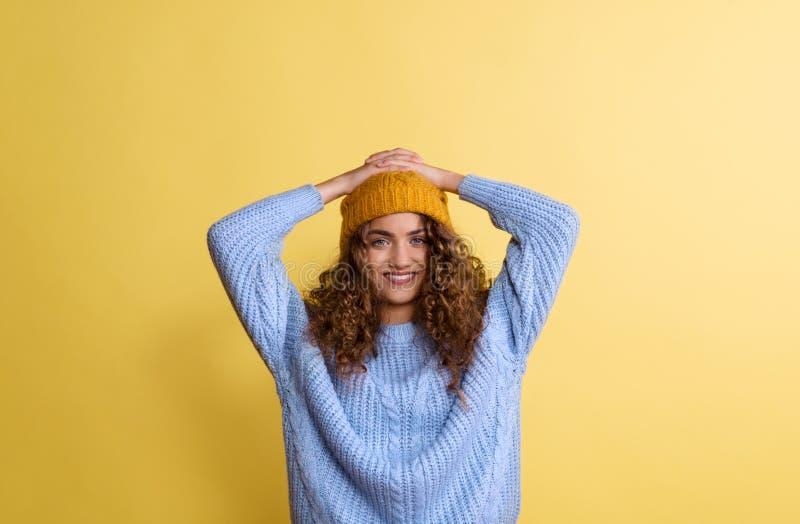 Portr?t einer jungen Frau mit woolen Hut in einem Studio auf einem gelben Hintergrund stockfoto