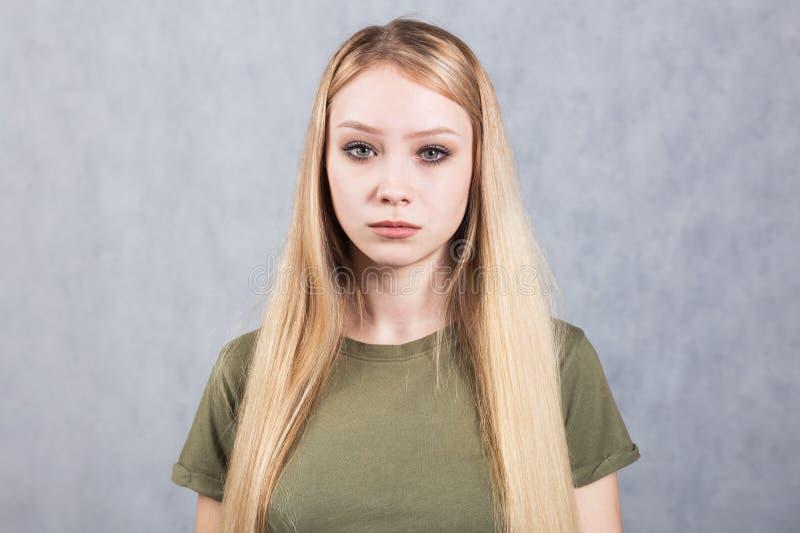 Portr?t einer jungen sch?nen traurigen Frau auf einem grauen Hintergrund lizenzfreie stockbilder