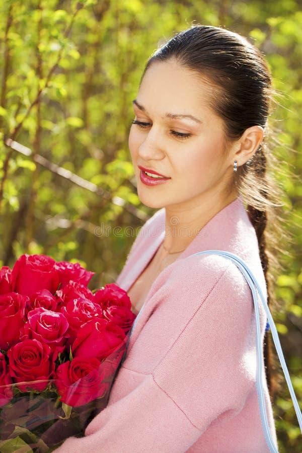 Portr?t einer jungen Sch?nheit mit einem Blumenstrau? des Parks der roten Rosen im Fr?hjahr lizenzfreies stockbild