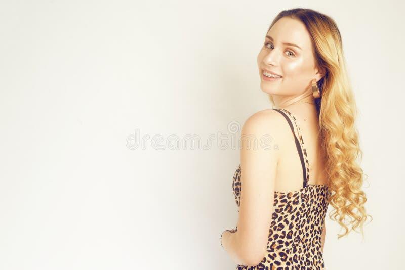 Portr?t einer sch?nen Blondine mit dem langen Haar Mädchen mit Goldohrringen, Modeschmuck, Kleid mit Leoparddruck Junges M?dchen  lizenzfreies stockfoto