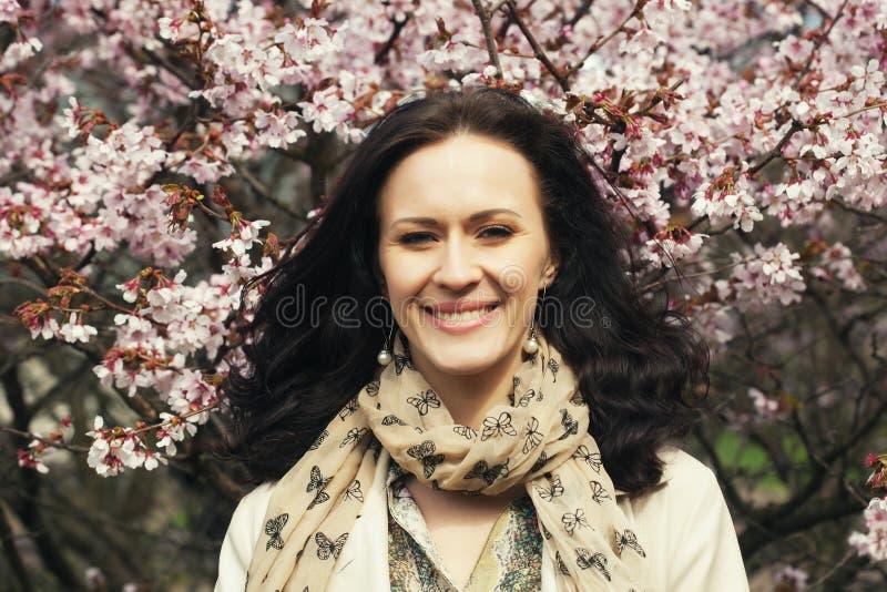 Portr?t einer sch?nen jungen Frau auf einem Hintergrund von rosa Kirschbl?ten im Fr?hjahr lizenzfreies stockfoto