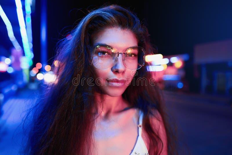 Portr?t einer sch?nen jungen Frau mit Gl?sern im futuristischen Neonlicht stockbilder