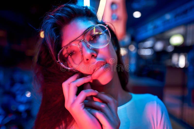 Portr?t einer sch?nen jungen Frau mit Gl?sern im futuristischen Neonlicht lizenzfreie stockfotos