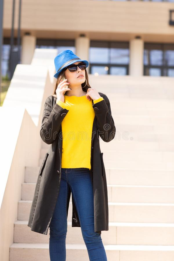 Portr?t einer sch?nen modernen stilvollen Frau in der hellen gelben Strickjacke und im blauen Hut Stra?enartschie?en stockfoto