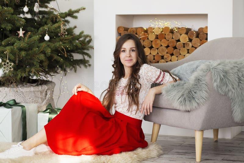 Portr?t einer Sch?nheit im Innenraum mit Weihnachtsdekorationen Gl?ckliche Frau nahe Weihnachtsbaum stockbilder