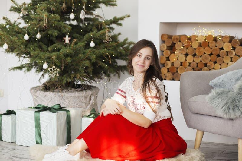 Portr?t einer Sch?nheit im Innenraum mit Weihnachtsdekorationen Gl?ckliche Frau nahe Weihnachtsbaum stockbild