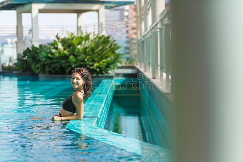 Portr?t einer sexy l?chelnden kaukasischen Frau in einem Badeanzug, der in einem Dachspitzenpool mit gr?nen B?schen und Stadtansi lizenzfreies stockfoto