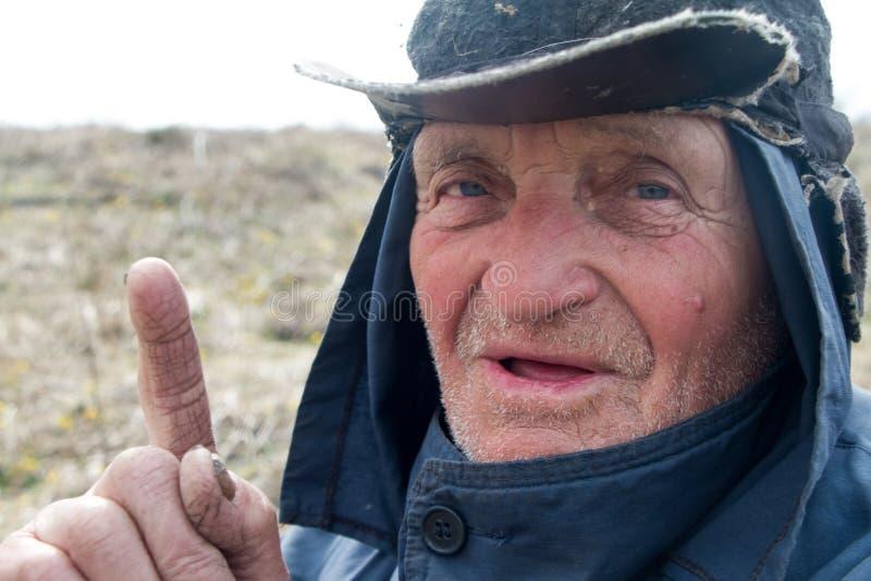 Portr?t eines alten Mannes in unordentliche Kleidung und Hut, die seinen Zeigefinger anhoben, habe ich eine Idee lizenzfreie stockfotografie