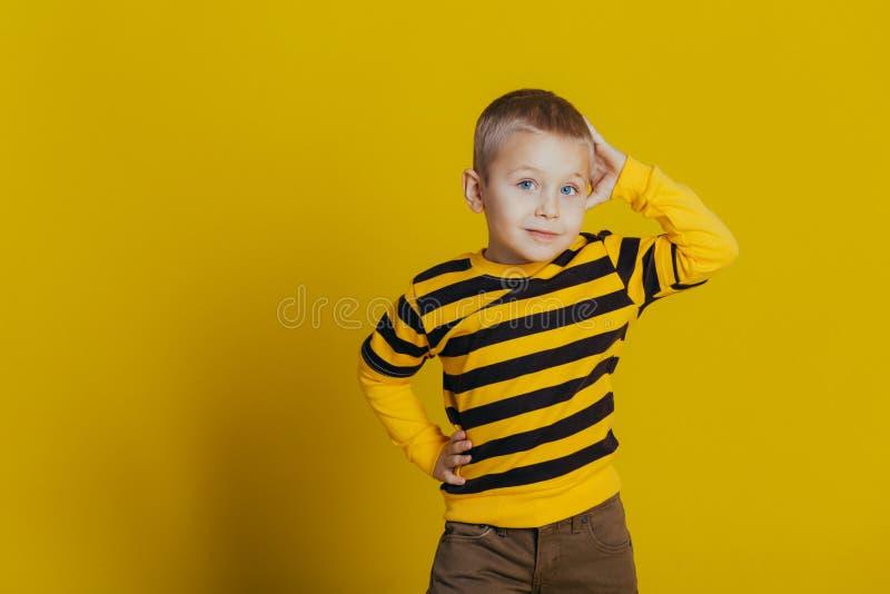 Portr?t eines attraktiven durchdachten Jungen in einer gestreiften Strickjacke, die eine Hand auf seinem Kopf auf einem gelben Hi stockbild