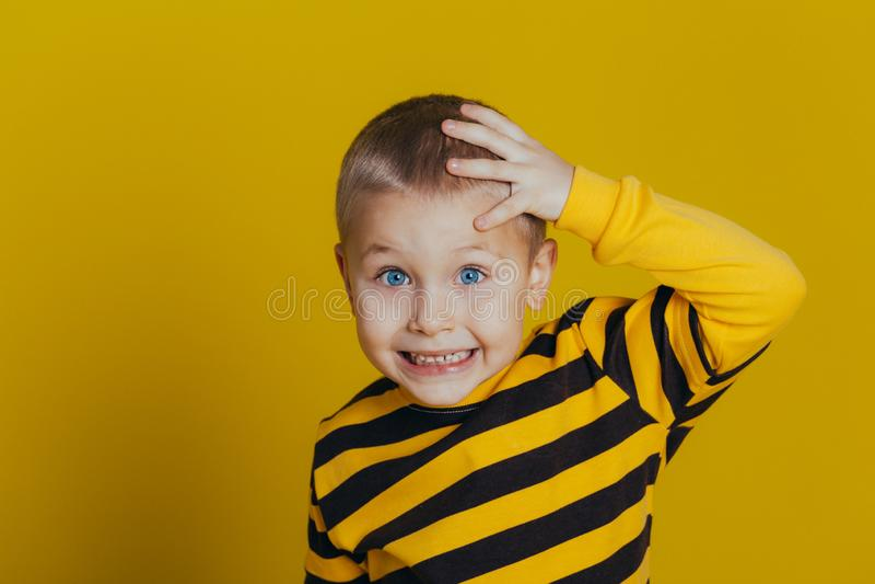 Portr?t eines attraktiven durchdachten Jungen in einer gestreiften Strickjacke, die eine Hand auf seinem Kopf auf einem gelben Hi lizenzfreies stockbild