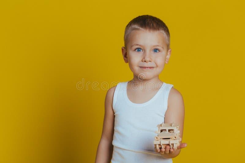 Portr?t eines attraktiven Jungen in einem wei?en T-Shirt, das h?lzerne Spielwaren auf einem gelben Hintergrund spielt stockbild