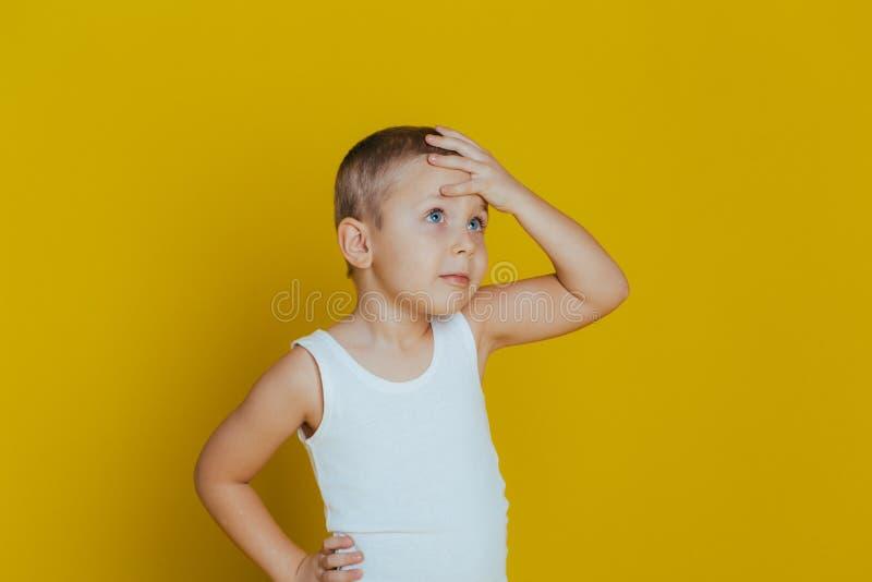 Portr?t eines attraktiven nachdenklichen kleinen Jungen mit in einer wei?en Weste, die eine Hand auf seinem Kopf h?lt stockbild