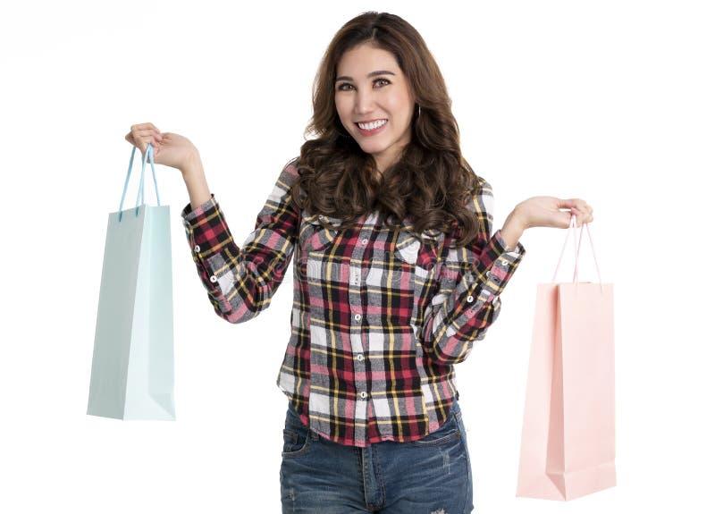 Portr?t eines aufgeregten sch?nen asiatischen M?dchens, das Einkaufstaschen lokalisiert auf wei?em Hintergrund h?lt lizenzfreie stockfotos