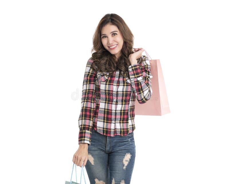 Portr?t eines aufgeregten sch?nen asiatischen M?dchens, das Einkaufstaschen lokalisiert auf wei?em Hintergrund h?lt lizenzfreie stockbilder