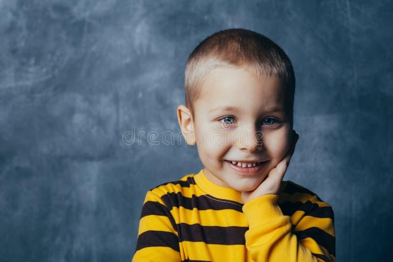 Portr?t eines durchdachten netten kleinen Kindes mit der Hand, die Gesicht, Kamera betrachtend ber?hrt stockbilder