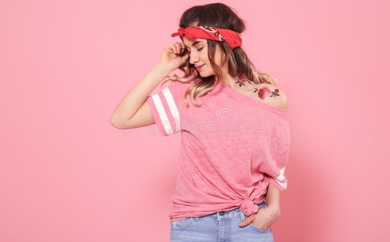 Portr?t eines Hippie-M?dchens mit T?towierung, auf rosa Hintergrund lizenzfreie stockbilder