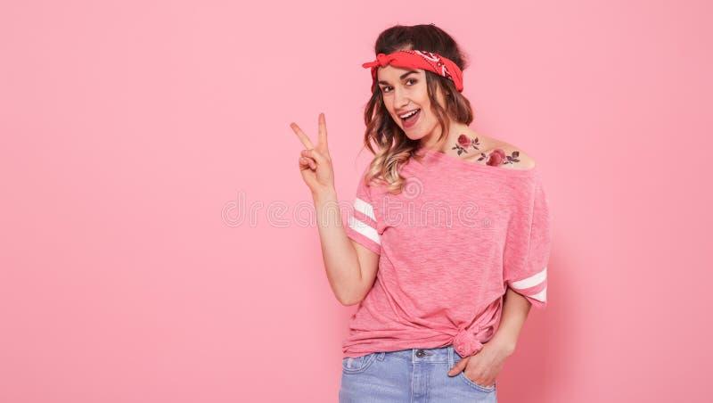 Portr?t eines Hippie-M?dchens mit T?towierung, lokalisiert auf rosa Hintergrund lizenzfreies stockfoto
