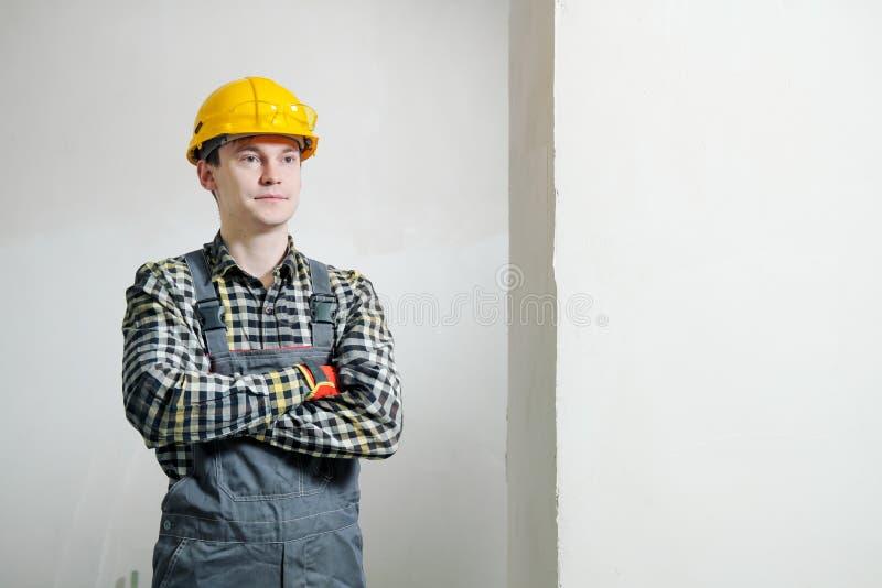 Portr?t eines jungen m?nnlichen Erbauers und des Schlossers in einem gelben Sturzhelm vor dem hintergrund einer Wand stockfotografie