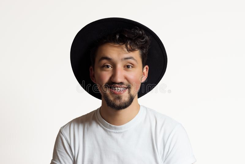 Portr?t eines jungen Mannes mit dem Klammerl?cheln Ein glücklicher junger Mann mit Klammern und ein Hut auf einem weißen Hintergr stockfotografie