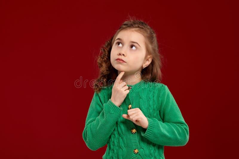 Portr?t eines kleinen brunette M?dchens mit einem langen, gelockten Haar, das gegen einen roten Hintergrund aufwirft stockbilder
