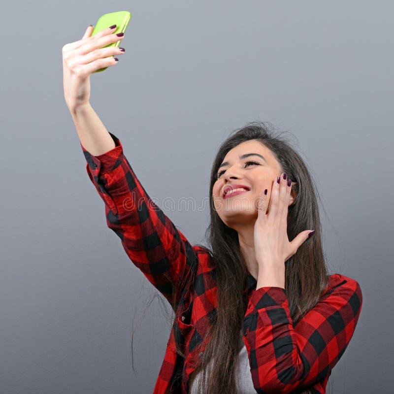 Portr?t eines M?dchens, das selfie mit Mobiltelefon gegen grauen Hintergrund nimmt lizenzfreies stockbild