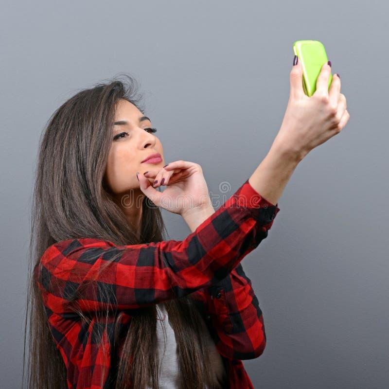 Portr?t eines M?dchens, das selfie mit Mobiltelefon gegen grauen Hintergrund nimmt lizenzfreie stockfotografie