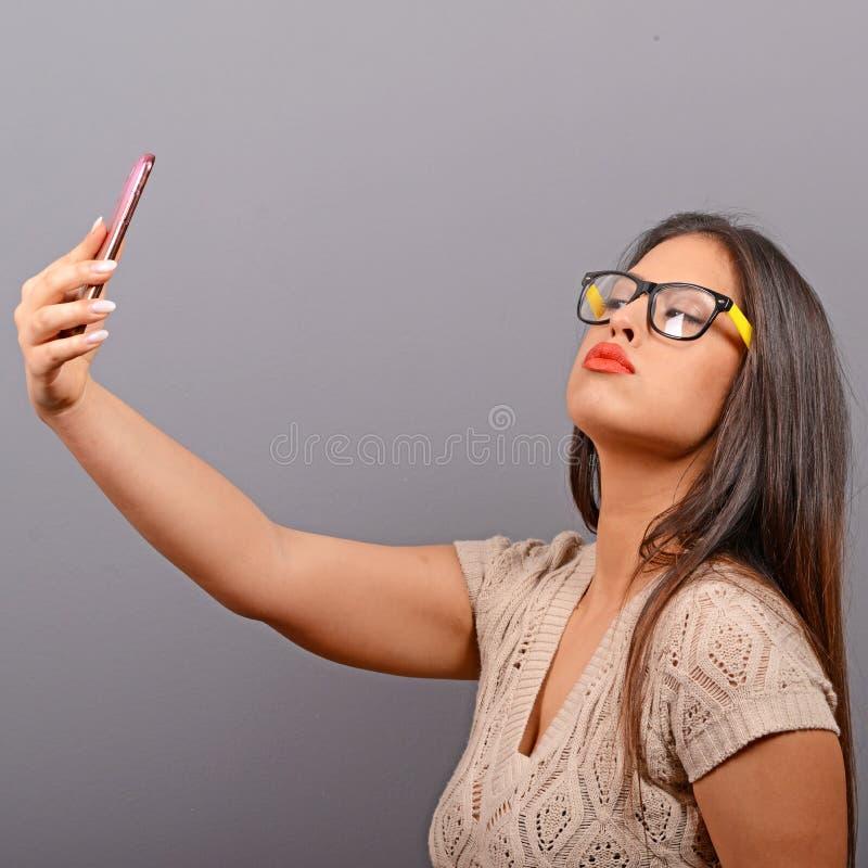 Portr?t eines M?dchens, das selfie mit Mobiltelefon gegen grauen Hintergrund nimmt stockfotografie