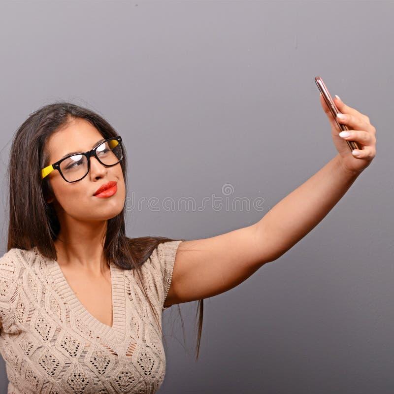 Portr?t eines M?dchens, das selfie mit Mobiltelefon gegen grauen Hintergrund nimmt lizenzfreies stockfoto