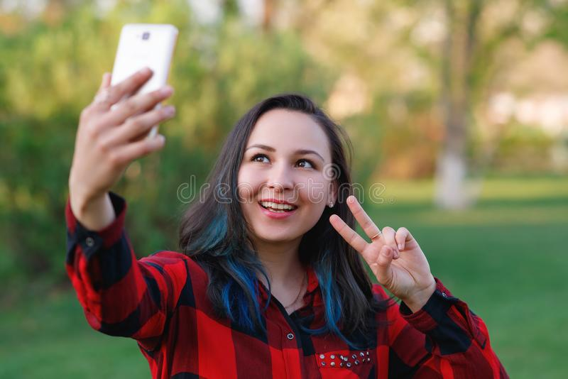 Portr?t eines sch?nen junge Frau selfie im Park mit einem Smartphone, der v-Zeichen tut lizenzfreies stockbild