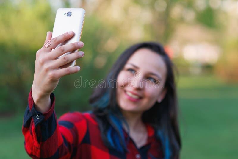 Portr?t eines sch?nen junge Frau selfie im Park mit einem Smartphone, der v-Zeichen tut stockbilder