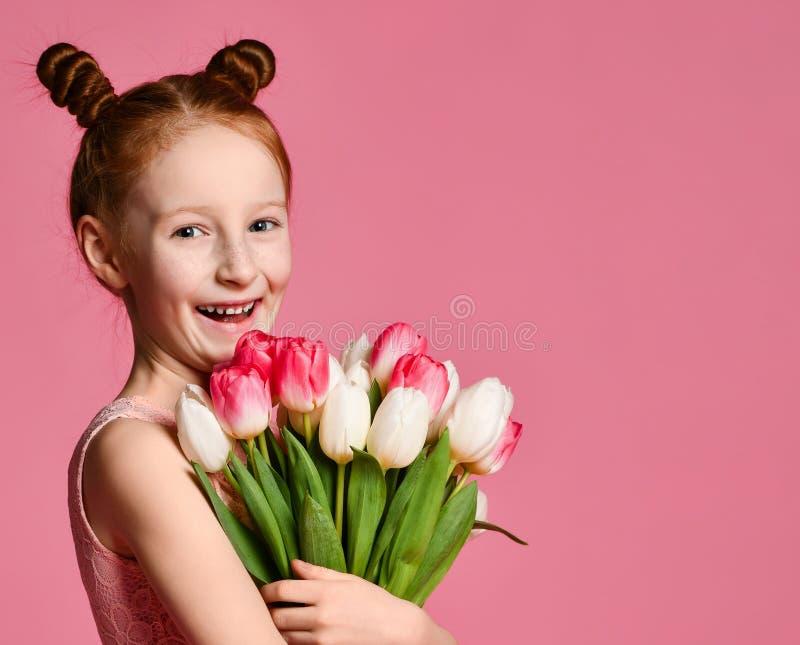 Portr?t eines sch?nen jungen M?dchens im Kleid, das gro?en Blumenstrau? der Iris und der Tulpen lokalisiert ?ber rosa Hintergrund stockbilder
