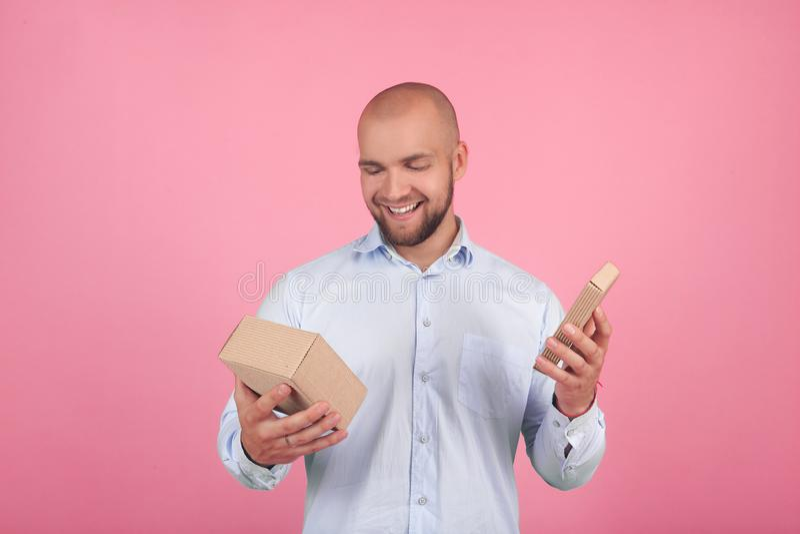 Portr?t eines sch?nen kahlen Mannes mit einem Bart gekleidet in einem wei?en Hemd ?ffnet ein Geschenk mit frohen Gef?hlen St?nde  stockfotos