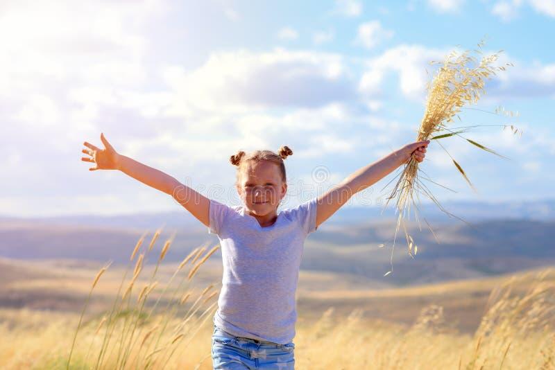 Portr?t eines sch?nen kleinen M?dchens mitten in einem Weizen-Feld stockfotografie