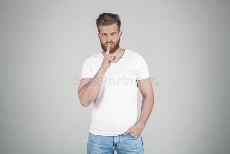 Portr?t eines sch?nen sexy b?rtigen Mannes Zeigt ein Zeichen der Ruhe er steht vor dem wei?en Hintergrund lizenzfreies stockbild