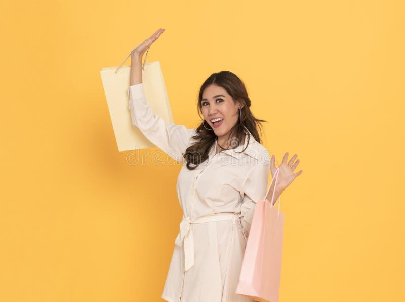 Portr?t eines tragenden Kleides des aufgeregten sch?nen asiatischen M?dchens, das Einkaufstaschen lokalisiert auf gelbem Hintergr stockfotos