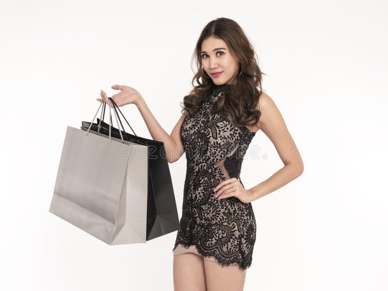 Portr?t eines tragenden Kleides des aufgeregten sch?nen asiatischen M?dchens und der halten Einkaufstaschen lokalisiert auf wei?e stockfoto