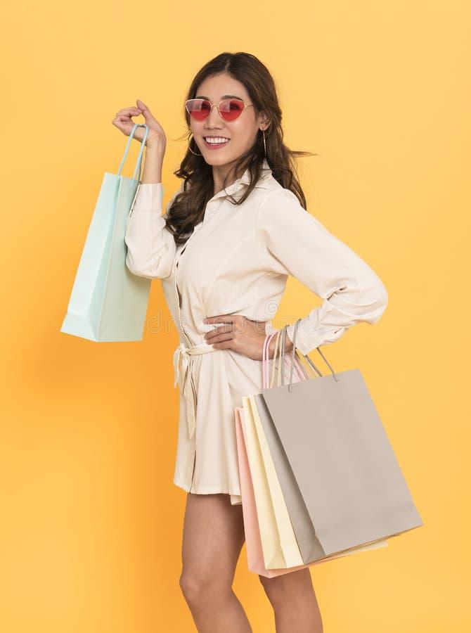 Portr?t eines tragenden Kleides und der Sonnenbrille des aufgeregten sch?nen asiatischen M?dchens, die Einkaufstaschen lokalisier lizenzfreie stockfotos
