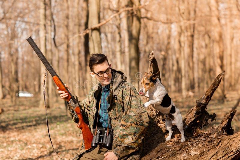 Portr?t eines Yang-J?gers mit einem Hund auf dem Wald lizenzfreie stockfotos
