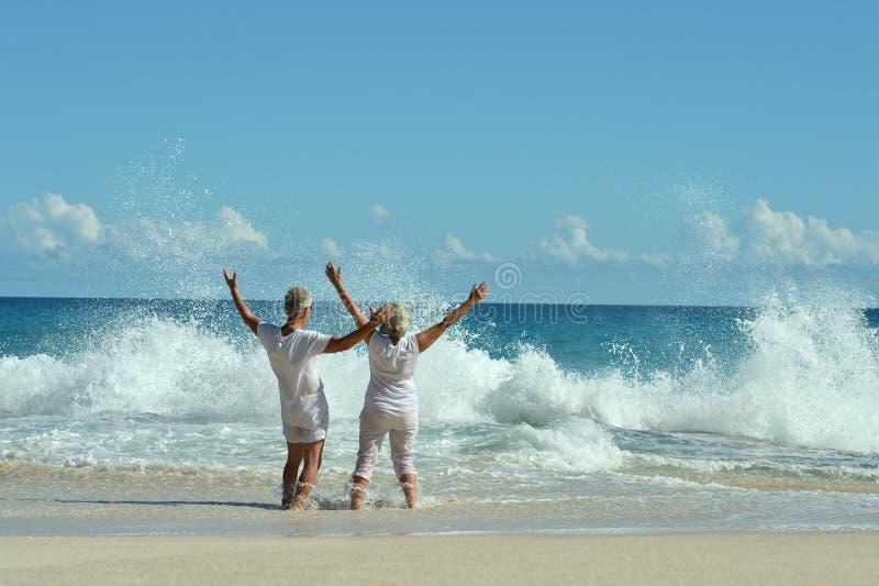 Portr?t von den gl?cklichen ?lteren Paaren, die auf wellenartig bewegenden H?nden des Strandes stillstehen stockbild