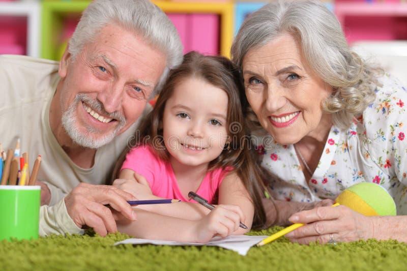 Portr?t von den Gro?eltern, die mit ihrem grandaughter beim L?gen auf Boden spielen stockbild