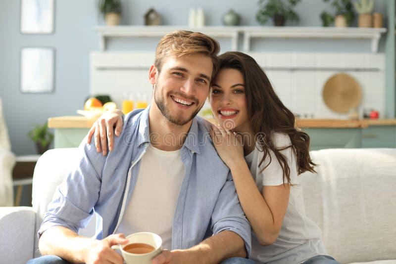 Portr?t von den netten jungen Paaren, die im Sofa sitzen lizenzfreie stockfotos