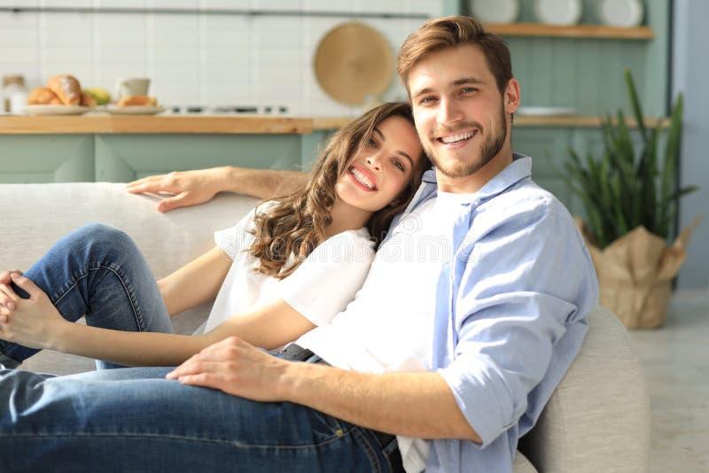 Portr?t von den netten jungen Paaren, die im Sofa sitzen lizenzfreies stockbild