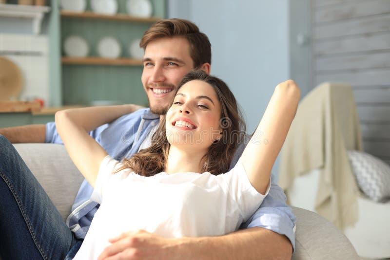 Portr?t von den netten jungen Paaren, die im Sofa sitzen stockbild