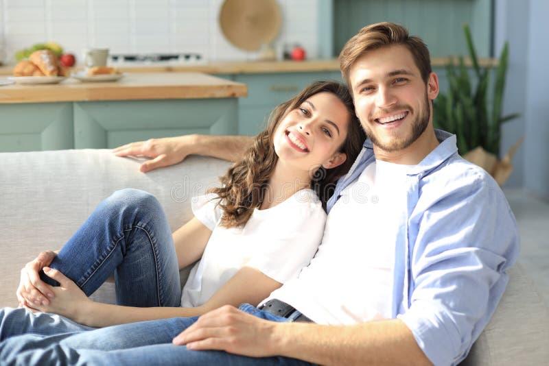 Portr?t von den netten jungen Paaren, die im Sofa sitzen stockbilder