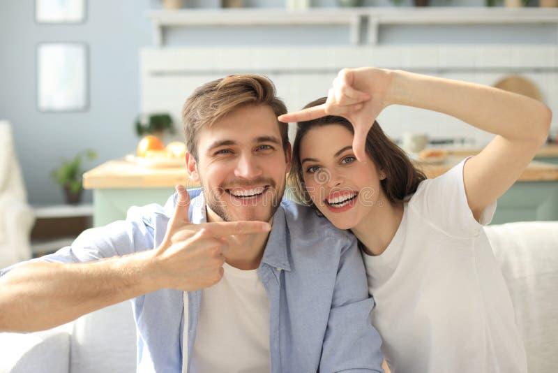 Portr?t von den netten jungen Paaren, die, sitzend im Sofa zeigen und lachen lizenzfreie stockfotos
