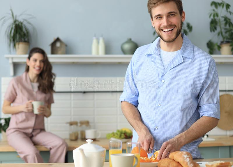 Portr?t von gl?cklichen jungen Paaren in den Pyjamas, die zusammen morgens in der K?che, trinkender Orangensaft zu Hause kochen stockfotografie